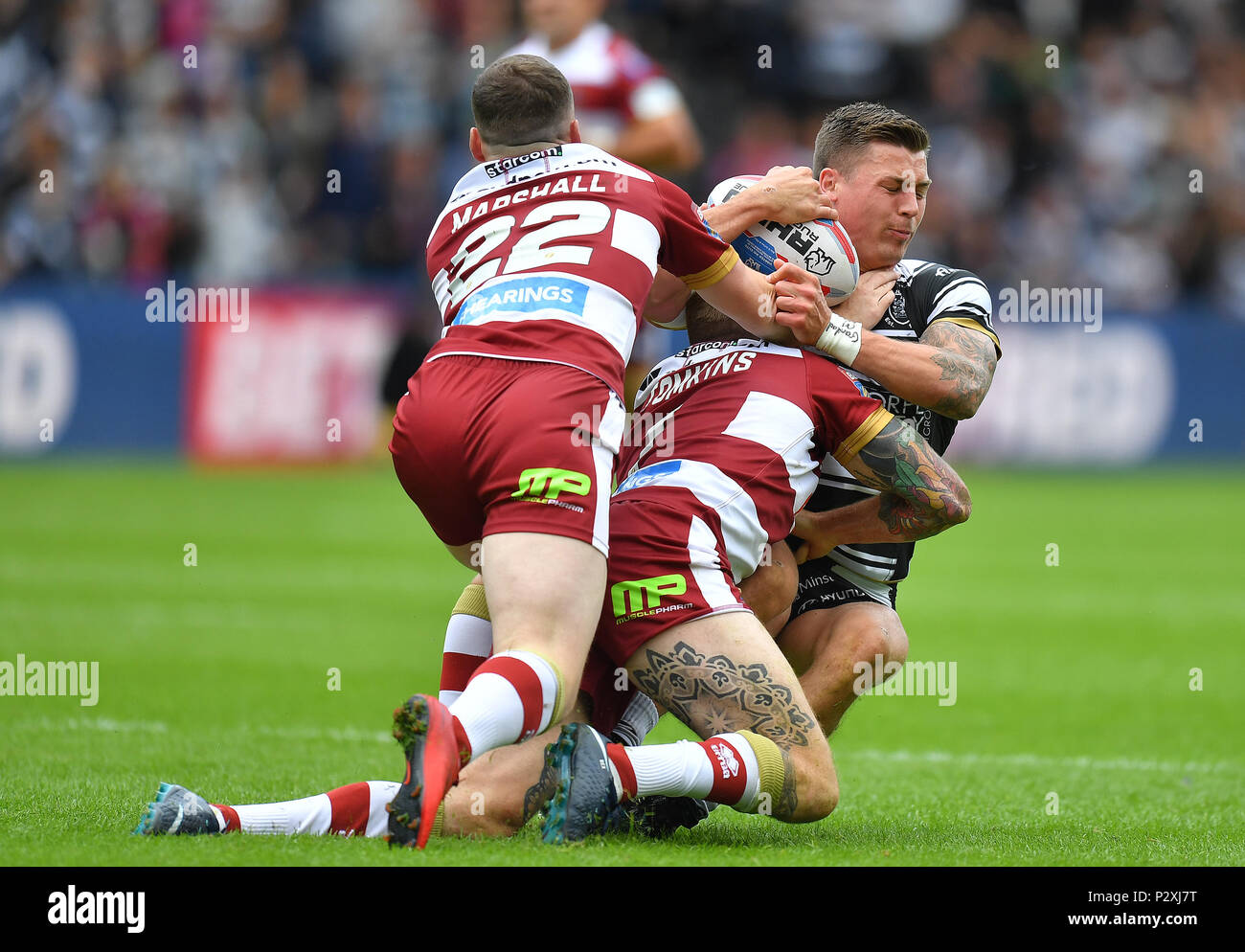 Hull FC's Jamie Shaul is tackled by Wigan Warriors' Sam Tomkins and Liam Marshall during the Betfred Super League match at the KCOM Stadium, Hull. - Stock Image