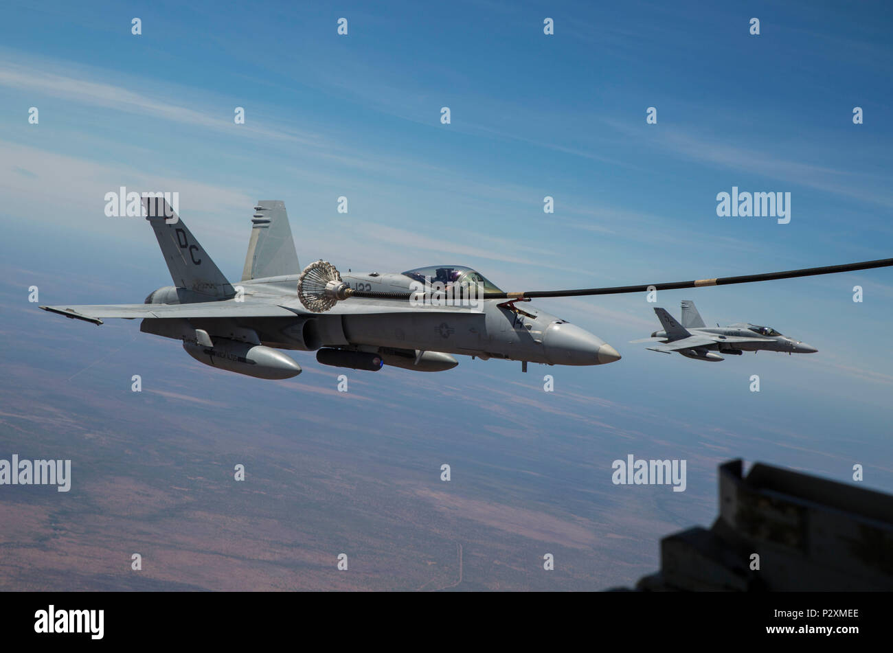 An F/A-18C Hornet with Marine Fighter Attack Squadron (VMFA) 122 moves in to catch the basket during an aerial refueling mission with Marine Aerial Refueler Transport Squadron (VMGR) 152 at Royal Australian Air Force Base Tindal, Australia during Exercise Pitch Black 2016, Aug. 9, 2016. VMGR-152 provides aerial refueling and assault support during expeditionary and joint or combined operations like Pitch Black. This exercise is a biennial, three week, multinational, large-force training exercise hosted by RAAF Tindal. (U.S. Marine Corps photo by Cpl. Nicole Zurbrugg) - Stock Image