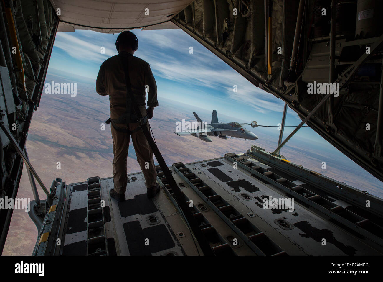 U.S. Marine Corps Cpl. Chris Lawler, a crewmaster with Marine Aerial Refueler Transport Squadron (VMGR) 152, observes an F/A-18C Hornet with Marine Fighter Attack Squadron (VMFA) 122 approach the refueling hose during Exercise Pitch Black 2016 at Royal Australian Air Force Base Tindal, Australia, Aug. 9, 2016. VMGR-152 provides aerial refueling and assault support during expeditionary, joint and combined operations like Pitch Black. This exercise is a biennial, three week, multinational, large-force training exercise hosted by RAAF Tindal. (U.S. Marine Corps photo by Cpl. Nicole Zurbrugg) - Stock Image