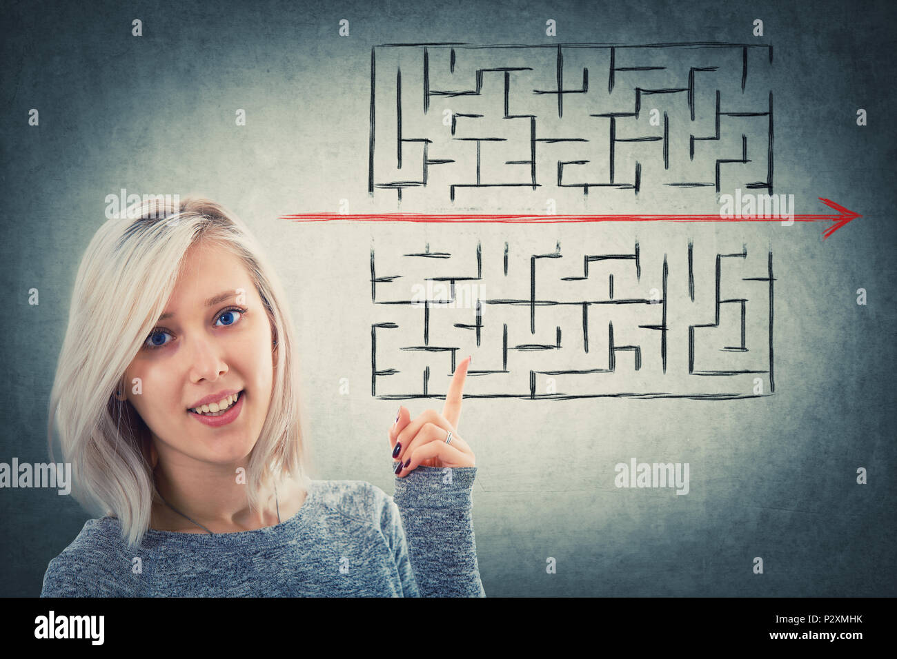 Close up portrait of a puzzled woman pointing her finger up showing a solution to escape from labyrinth. Young businesswoman breaking the rules, as a  - Stock Image