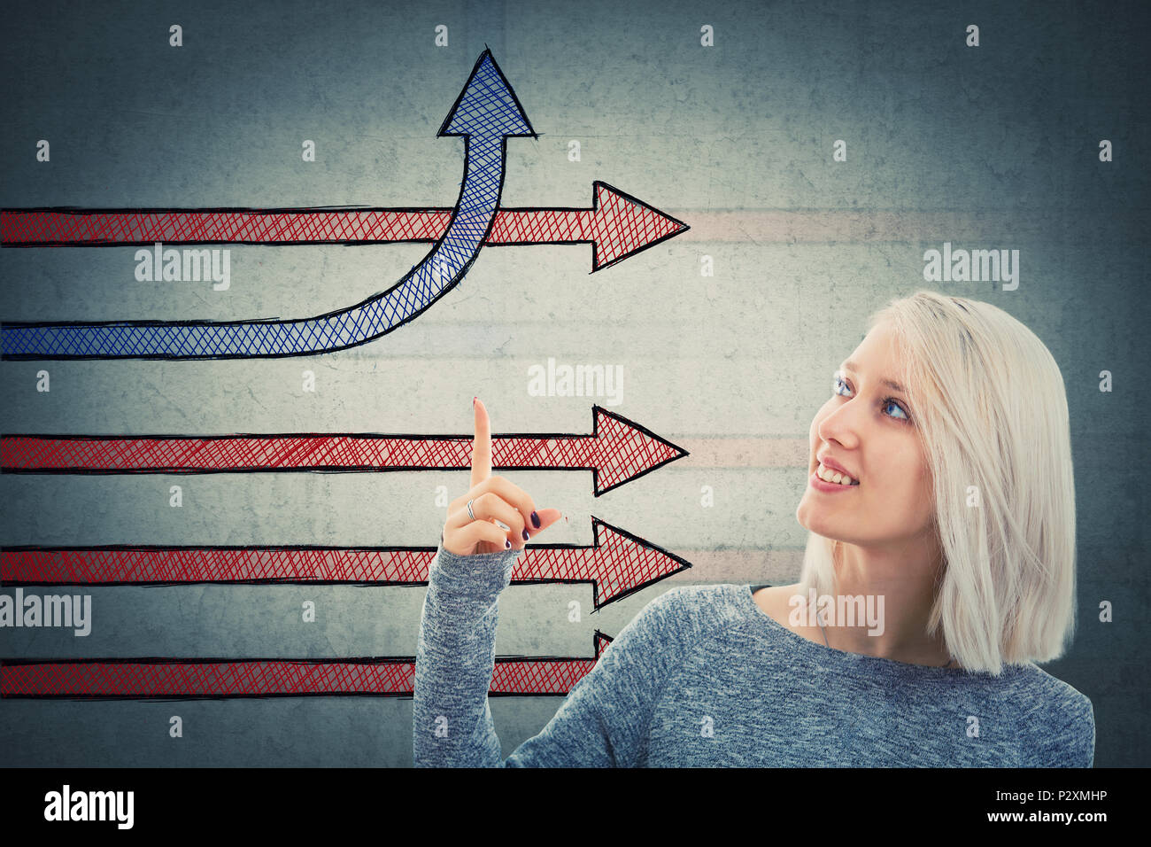 Smiling woman showing imaginative arrows with index finger one change direction bending and going up. Different business thinking, creativity and comp - Stock Image