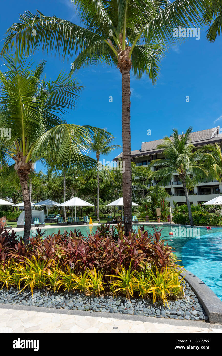 Lush gardens lead down to the pool at the Shangri La Rasa Ria Hotel and Resort in Kota Kinabalu, Borneo on the edge of the South China Sea - Stock Image