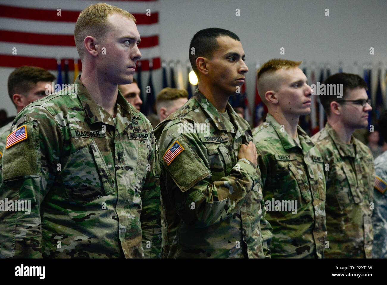 GRAFENWOEHR, Germany – (From left to right) 1st Lt. Ethan Klausner, Sgt. Andres Quintero and Pfc. Shawn Bailey of the 2nd Cavalry Regiment and 2nd Lt. Justin Ganzer of the 21st Theater Sustainment Command stand during the National Anthem during the 2016 European Best Warrior Competition concluding ceremony held at the Grafenwoehr Physical Fitness Center. The intense, grueling annual weeklong competition is the most prestigious competitive event of the region. (U.S. Army Photo by Pfc. Emily Houdershieldt) - Stock Image