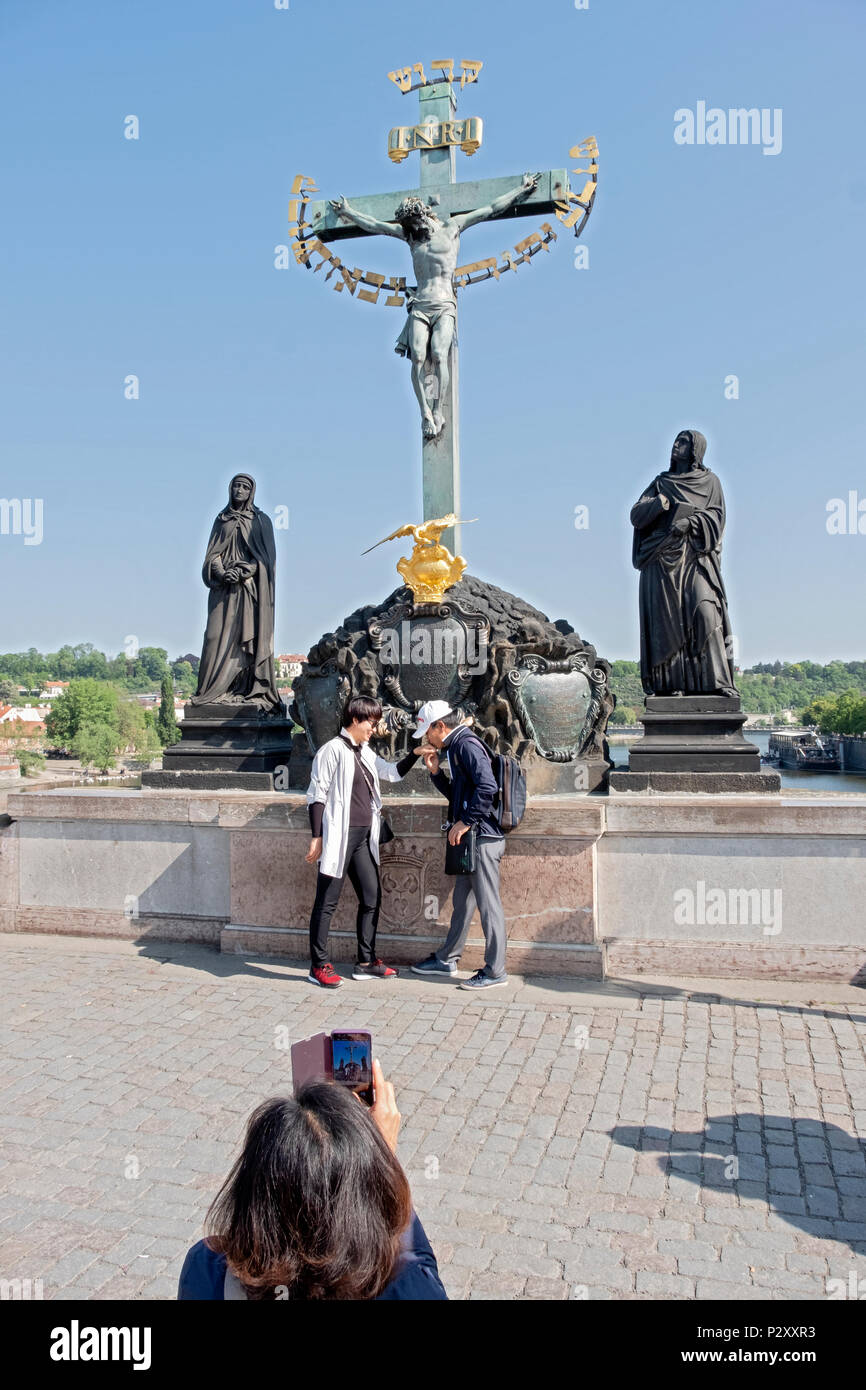 An Asian couple poses for a photo on the Charles Bridge in