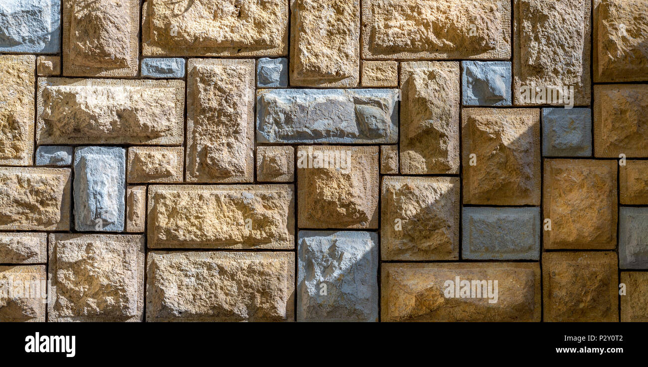 Background of pattern of beige and gray decorative uneven stone wall surface - Stock Image