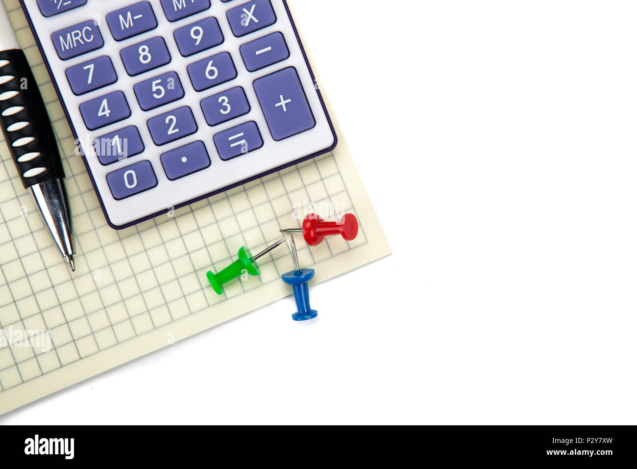 One big calculator and stationery on a white table closeup - Stock Image