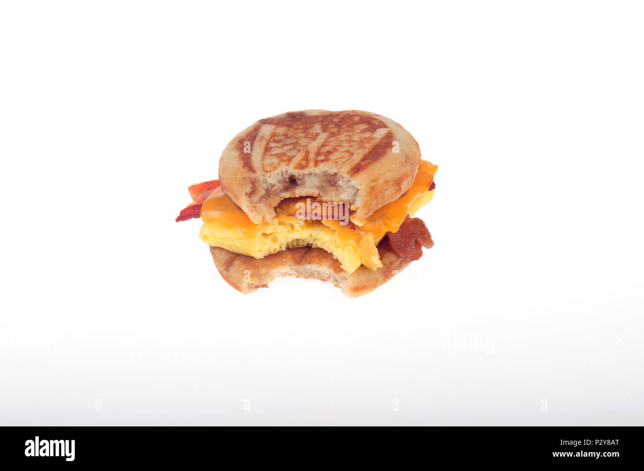 McDonald's McGriddle bacon, egg and cheese breakfast fast food sandwich with bite taken out isolated on white - Stock Image