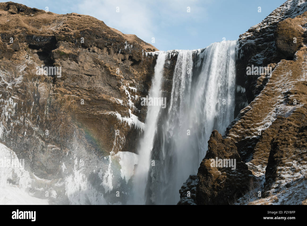 Skógafoss waterfall from below, on a sunny day with a rainbow in the mist. Landscape orientation. - Stock Image