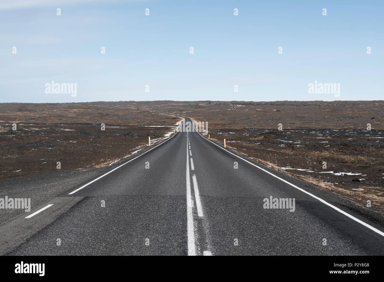 Empty Icelandic road stretching off into the horizon through lava fields on a clear sunny day. - Stock Image