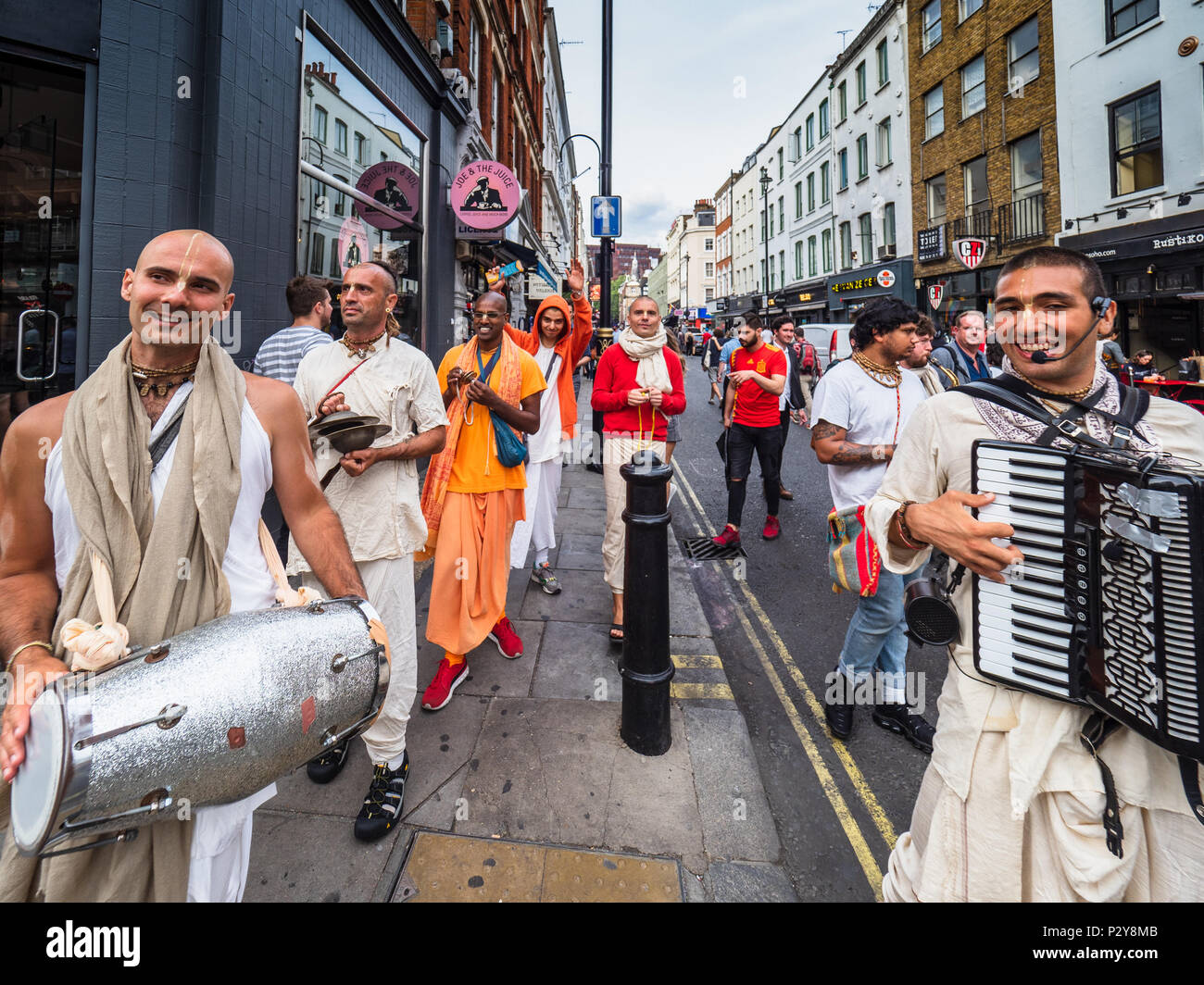 Hare Krishna Chanters move through Old Compton Street in London's Soho district handing out invites for free food at the Radha Krishna Temple. - Stock Image