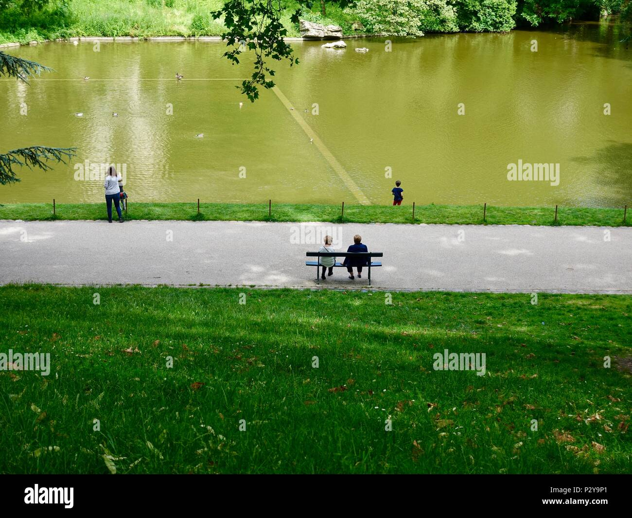 Two women sit on a bench overlooking the lake at Parc Buttes Chaumont, Paris, France - Stock Image