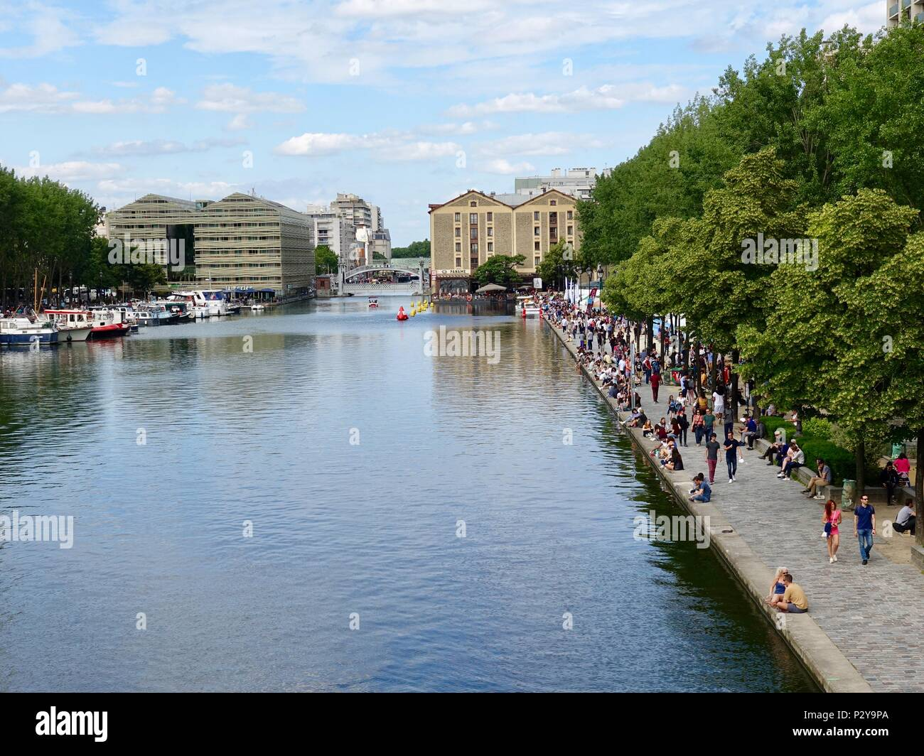 People line the banks of the canal on a warm Saturday afternoon at at Bassin de la Villette, Paris, France - Stock Image
