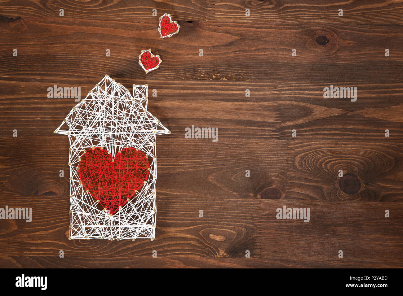 Home sweet home. Handmade home symbol with heart shape on wooden background with copy space - Stock Image