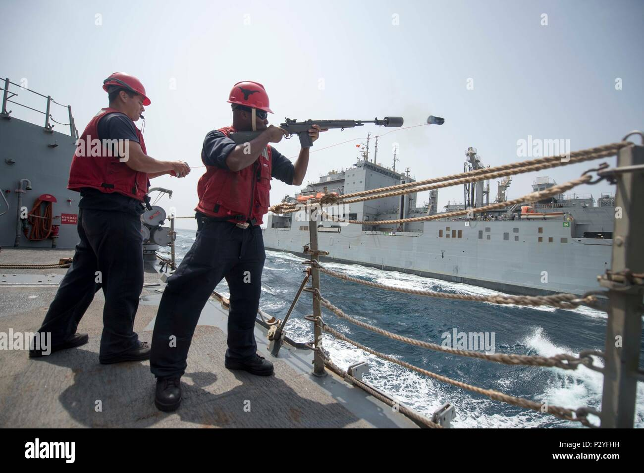 160808-N-DQ503-010    GULF OF ADEN (Aug. 8, 2016) Gunner's Mate 2nd Class Allen Marshall fires a shot line from the guided-missile destroyer USS Roosevelt (DDG 80) to the dry cargo/ammunition ship USNS Cesar Chavez (T-AKE 14). Roosevelt, deployed as part of the Eisenhower Carrier Strike Group, is supporting maritime security operations and theater security cooperation efforts in the U.S. 5th Fleet area of operations. (U.S. Navy photo by Mass Communication Specialist 3rd Class Taylor A. Elberg/Released) - Stock Image