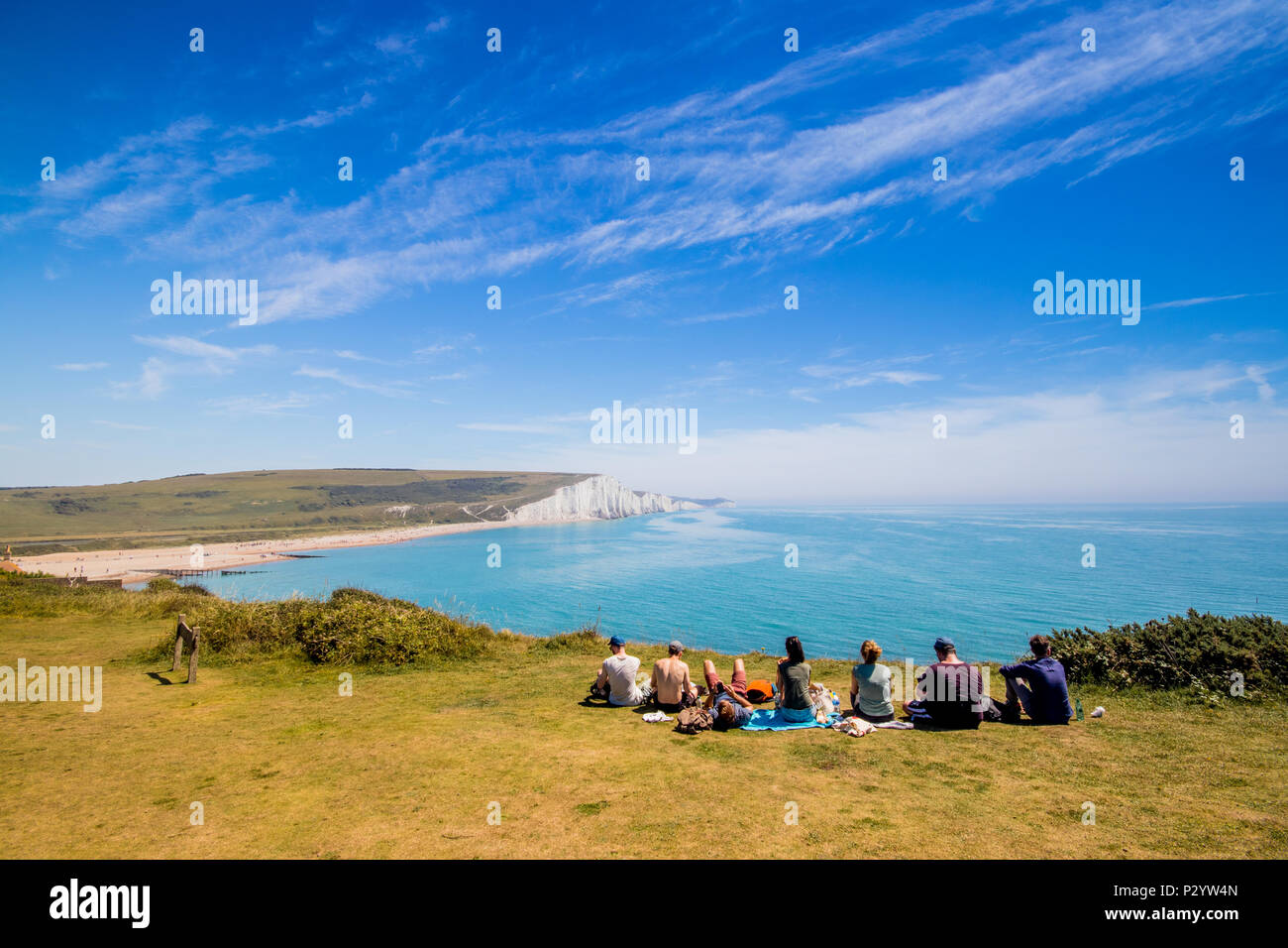 Walkers sitting at the cliff edge looking towards Cuckmere Haven, Seven Sisters Country Park near Eastbourne, East Sussex, UK - Stock Image