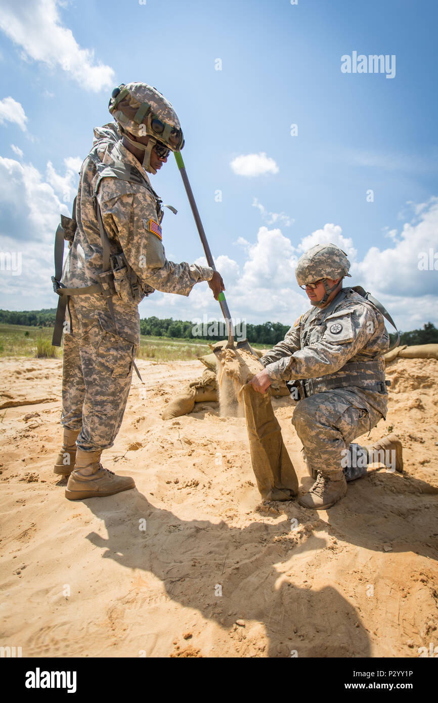 U.S. Army Spc. Partick Taylor (left) and Pvt. Daniel Santamaria, 304th Quartermaster West Hartford, Conn., fill sand bags for a defensive fighting position during Combat Support Training Exercise (CSTX) 86-16-03 at Fort McCoy, Wis., August 10, 2016. The 84th Training Command's third and final Combat Support Training Exercise of the year hosted by the 86th Training Division at Fort McCoy, Wis. is a multi-component and joint endeavor aligned with other reserve component exercises. (U.S. Army photo by Spc. John Russell/Released) - Stock Image