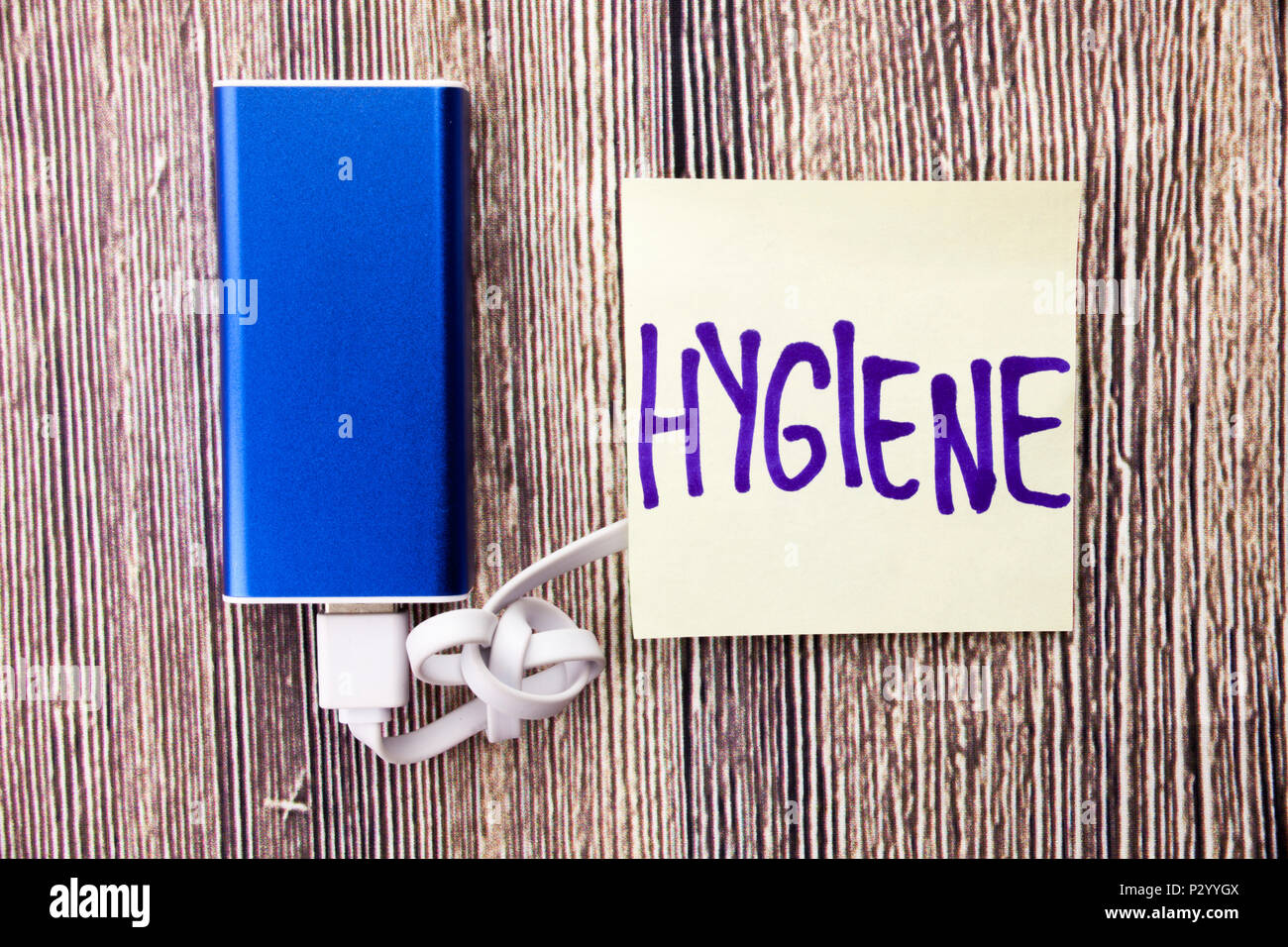 Health and hygiene concept on handwritten paper. Wooden retro background. Hygiene concept charged with powerbank. Powerbank with white paper - Stock Image