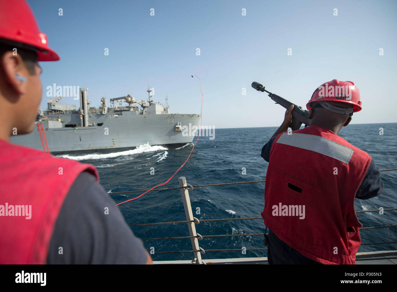 160814-N-DQ503-019     ARABIAN SEA (Aug. 14, 2016) Gunner's Mate 2nd Class Allen Marshall fires a shotline from the guided-missile destroyer USS Roosevelt (DDG 80) to the dry cargo and ammunition ship USNS Cesar Chavez (T-AKE 14) during a replenishment-at-sea. Roosevelt, deployed as part of the Eisenhower Carrier Strike Group, is supporting maritime security operations and theater security cooperation efforts in the U.S. 5th Fleet area of operations. (U.S. Navy photo by Mass Communication Specialist 3rd Class Taylor A. Elberg/Released) - Stock Image