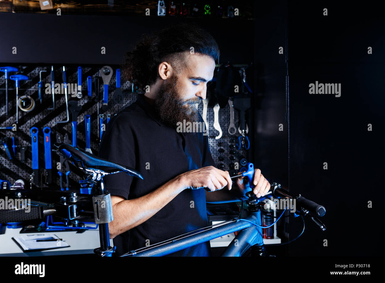 Theme sale and repair of bicycles. Young and stylish with a beard and long hair, a Caucasian man uses a tool to set up and repair a bike in a store. Business owner at work - Stock Image