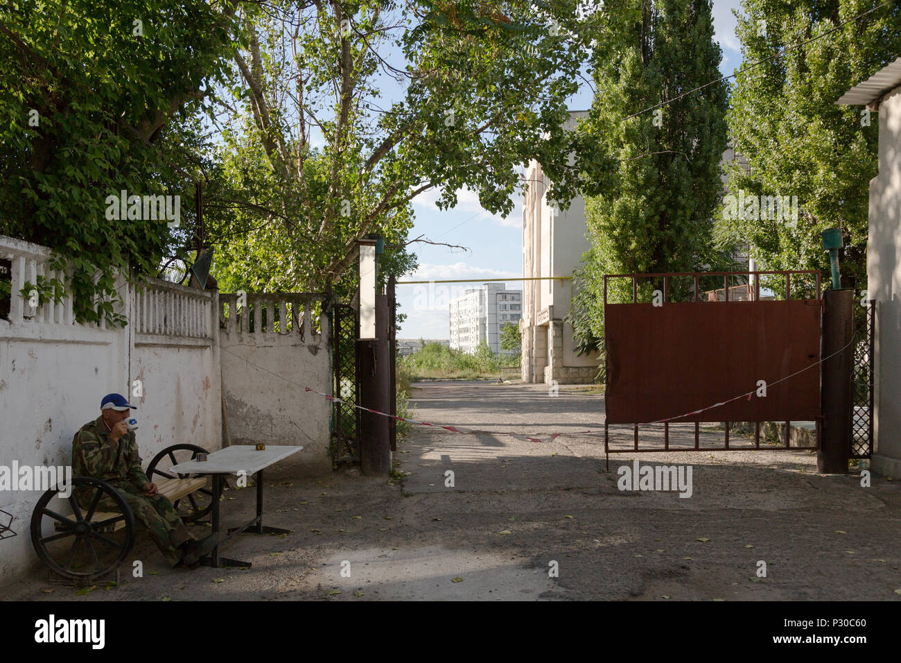 Bender, Moldova, gate to the premises of a closed factory - Stock Image