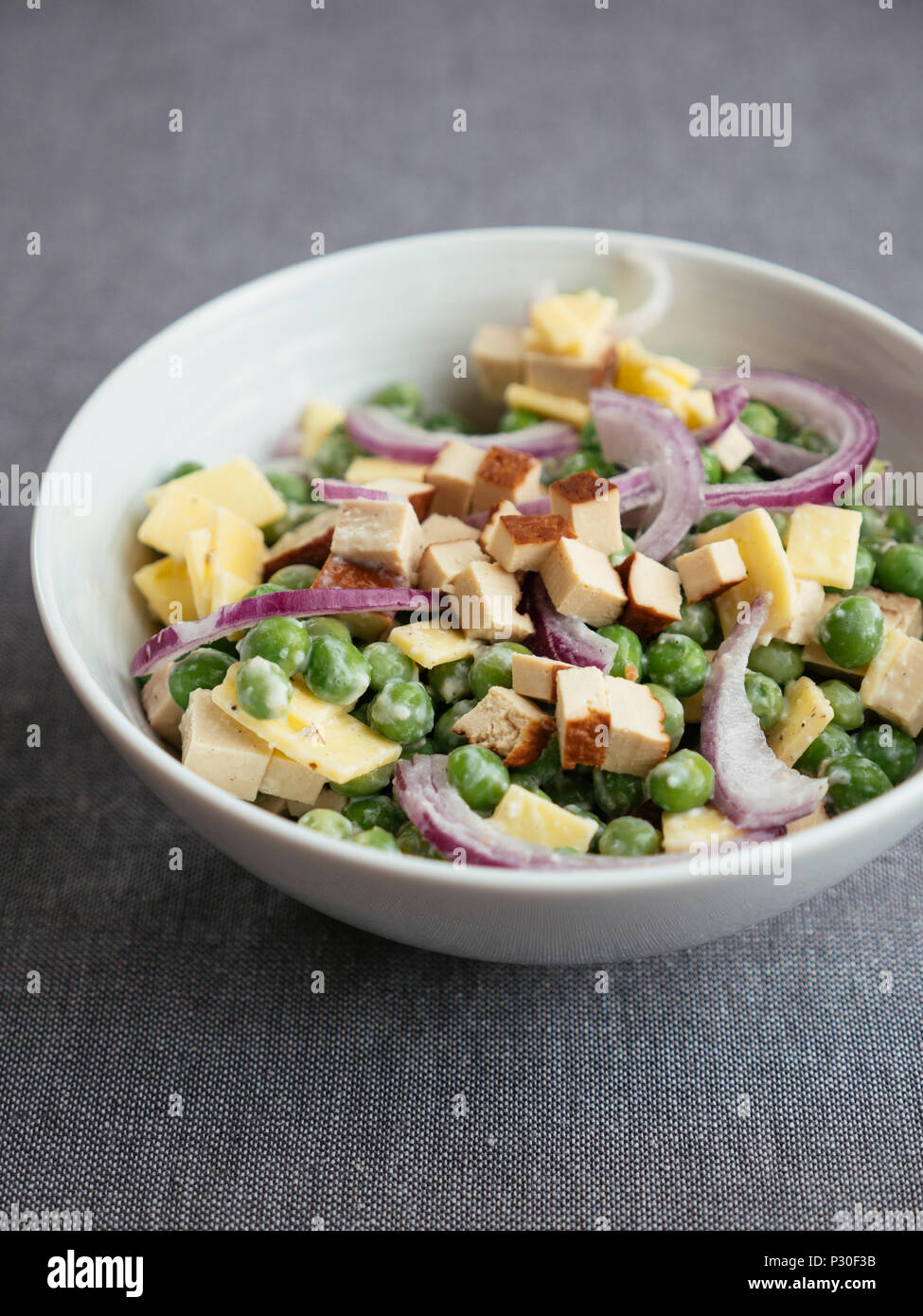 Vegan pea salad with tofu and vegan cheese Stock Photo