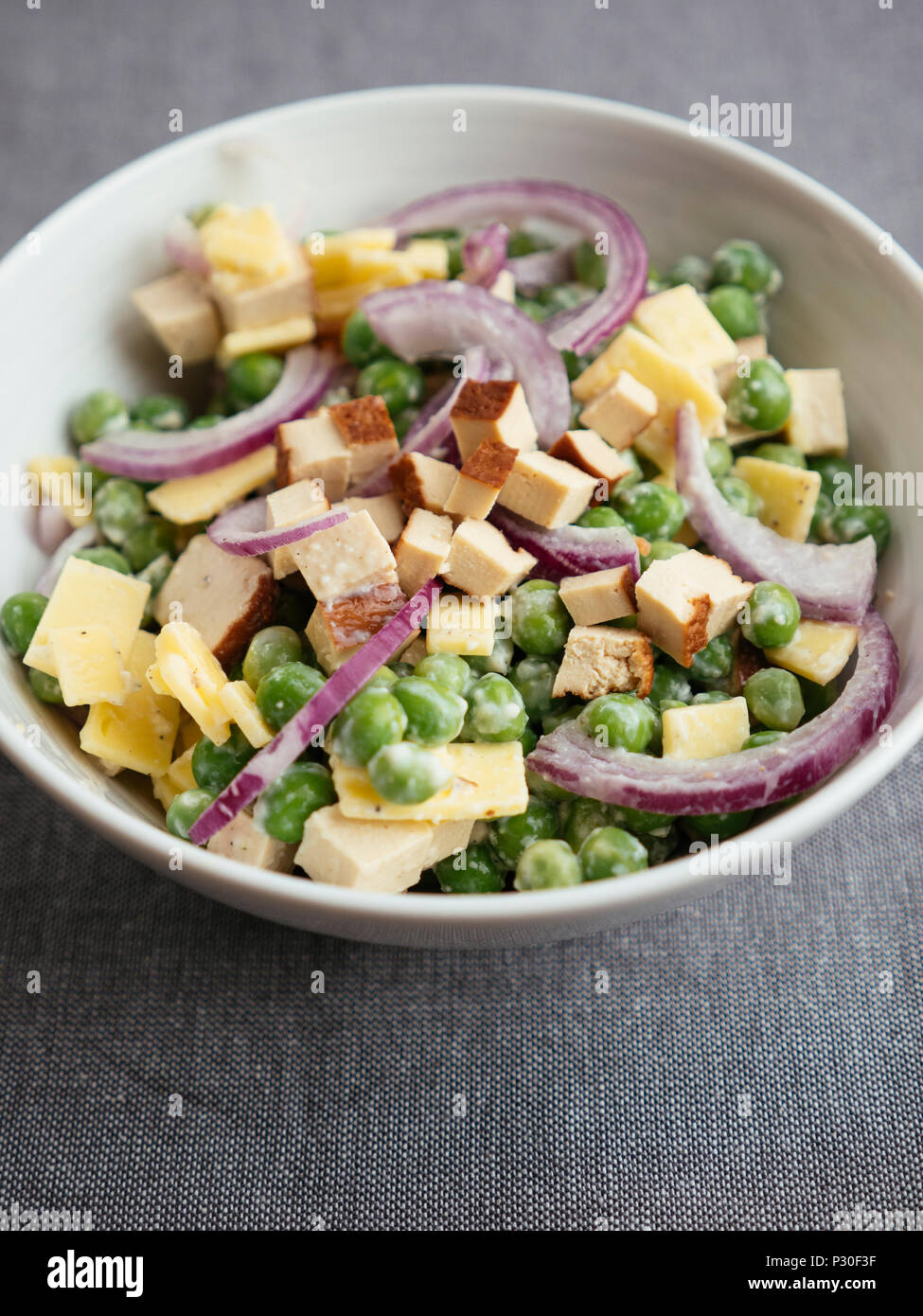 Vegan pea salad with tofu and vegan cheese - Stock Image