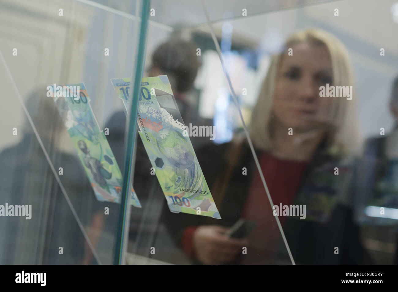 St. Petersburg, Russia - May 23, 2018: People at commemorative 100 rubles banknotes for FIFA World Cup Russia 2018 exposed in the exhibition '1818+. T - Stock Image