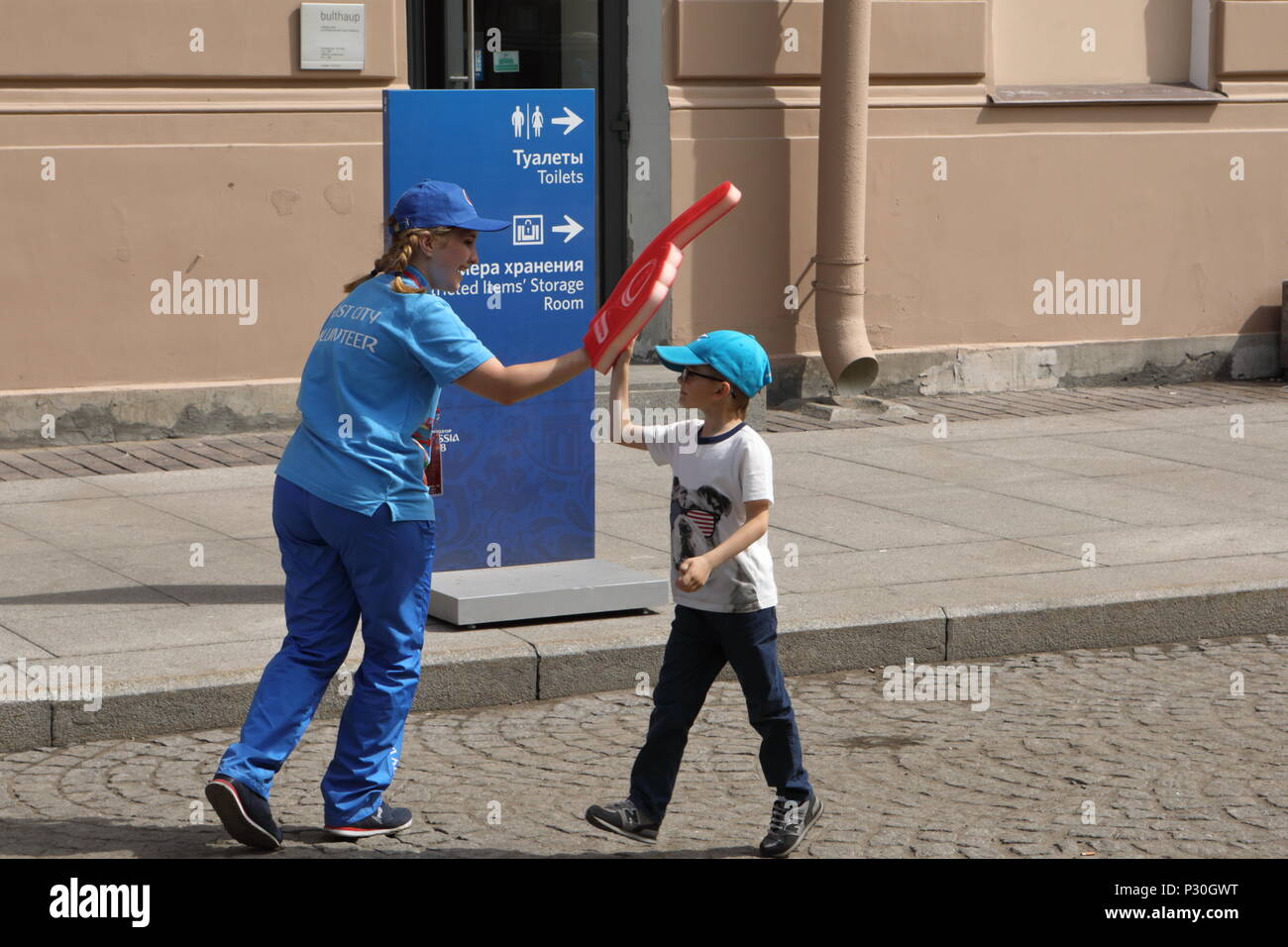 St. Petersburg, Russia - June 15, 2018: Girl volunteer of FIFA World Cup Russia 2018 on the street with pointing sign. 1733 volunteers help to FIFA Wo - Stock Image