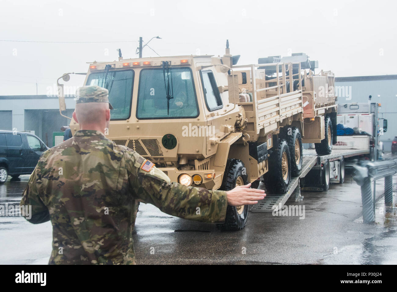A member from South Carolina Army National Guard's 263rd Army Air and Missile Defense Command ground-guides a Light Equipment Transport and trailer off of another transport flatbed at 22 Wing North Bay in preparation for the Vigilant Shield Air Defence Artillery Field Training Exercise on August 12, 2016. (Canadian Armed Forces photo by Cpl Joseph Morin) Stock Photo
