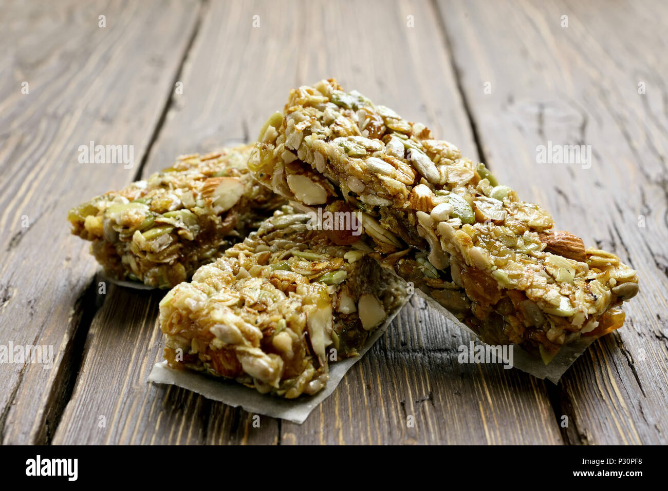 Healthy energy snack granola bars on wooden background. Close up view - Stock Image