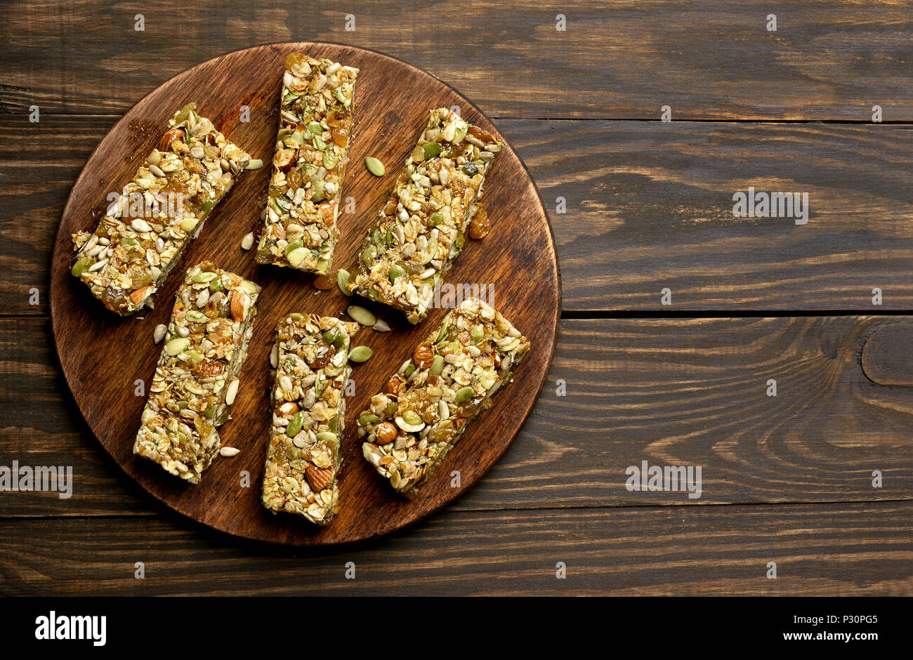 Granola bars. Healthy energy snack on wooden board. Top view, flat lay - Stock Image