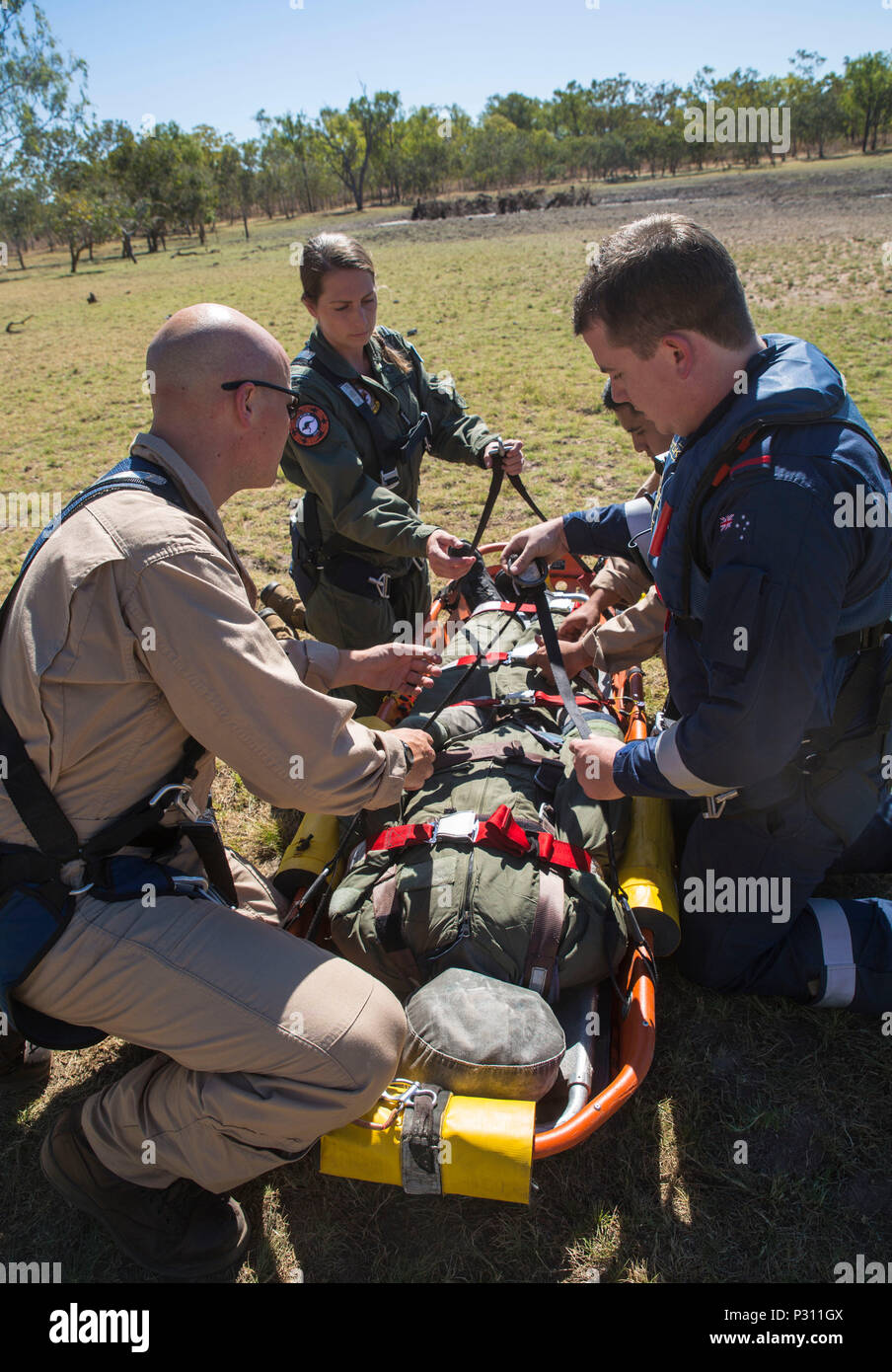 Marine Fighter Attack Squadron (VMFA) 122 U.S. Navy Lt. Matthew Case, flight surgeon, Kurt Pride, rescue crewman with RAAF Tindal Search and Rescue, and Flying Officer Kimberly MacDonald, a nurse with the Royal Australian Air Force, ensure that all buckles and clips are secure during SAR training at Exercise Pitch Black 2016, Royal Australian Air Force Base Tindal, Australia, Aug. 16, 2016. The SAR team trains with local and international forces during exercises like Pitch Black to ensure all medical personnel that can respond to an aircraft emergency are capable of carrying out the same proce - Stock Image