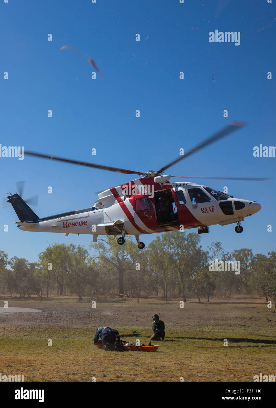 A Sikorsky S76A++ Search and Rescue helicopter approaches to hoist a stretcher during SAR training at Exercise Pitch Black 2016, Royal Australian Air Force Base Tindal, Australia, Aug.16, 2016. The SAR team trains with local and international forces during exercises like Pitch Black to ensure all medical personnel that can respond to an aircraft emergency are capable of carrying out the same procedures. The biennial, multinational exercise involves approximately 10 allied nations and prepares these forces for possible real-world scenarios. The bilateral effort amongst Exercise Pitch Black 2016 - Stock Image