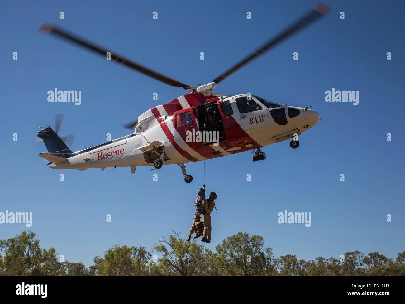 Marine Fighter Attack Squadron (VMFA) 122 U.S. Navy Lt. Matthew Case, flight surgeon, and U.S. Navy Petty Officer 3rd Class Juan Garcia, hospital corpsman, are hoisted into a Sikorsky S76A++ Search and Rescue helicopter while conducting SAR training during Exercise Pitch Black 2016 at Royal Australian Air Force Base Tindal, Australia, Aug. 16, 2016.  The SAR team trains with local and international forces during exercises like Pitch Black to ensure all medical personnel that can respond to an aircraft emergency are capable of carrying out the same procedures. The biennial, multinational exerci - Stock Image
