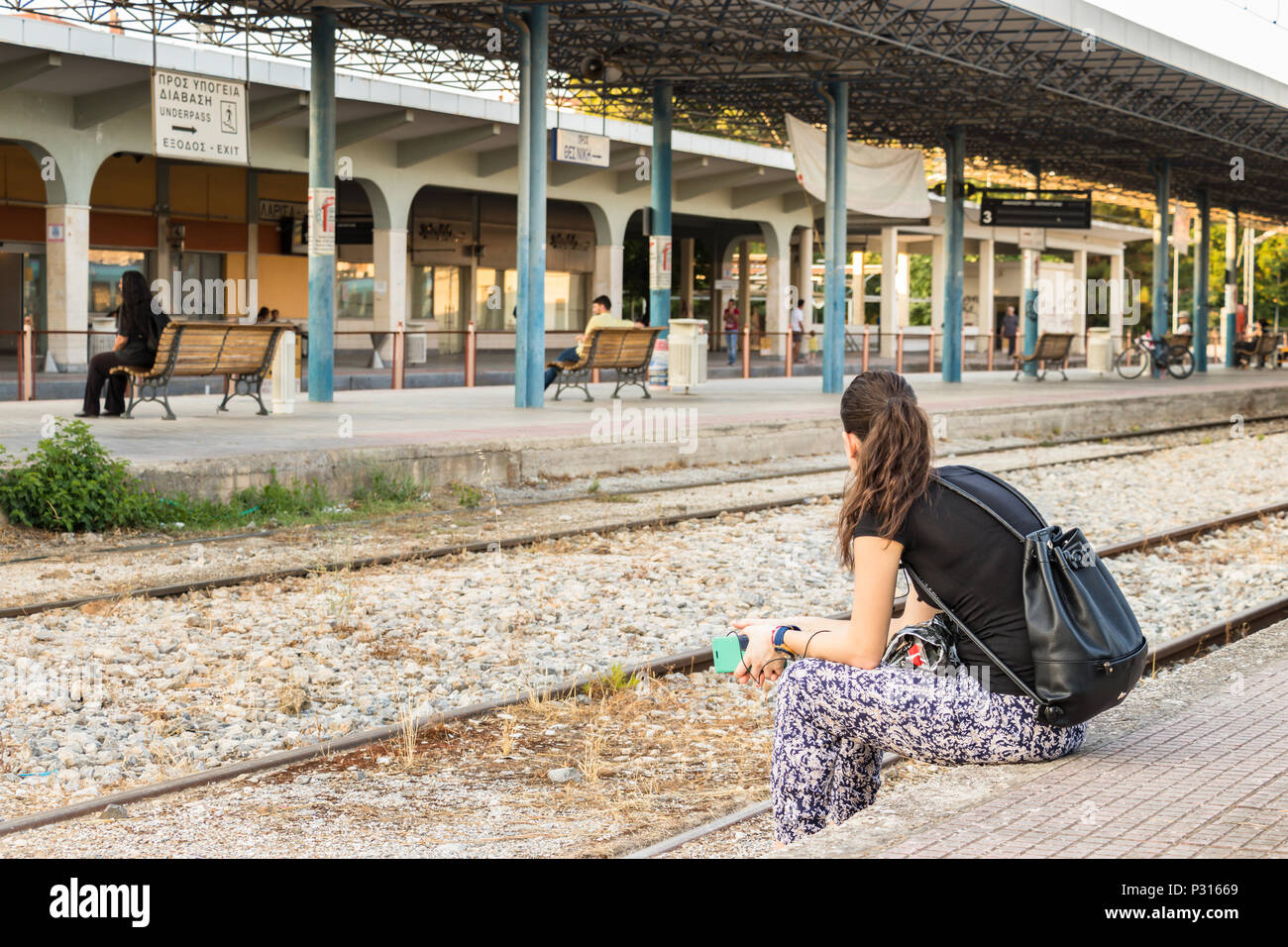 Larissa, Greece - June 11th, 2018: A young woman sitting looking away on the passengers platform in the Larissa train Station. - Stock Image