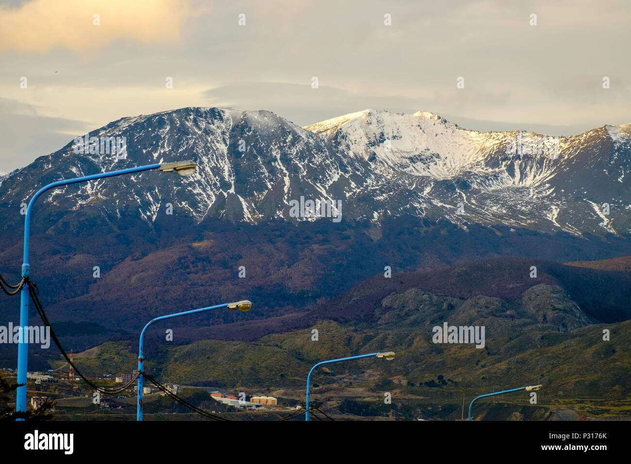 Blue street lights are standing above the streets of Ushuaia. In the background, the Martial mountain range received some fresh snow. Stock Photo