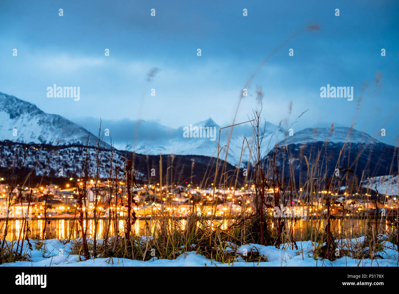 The city lights of Ushuaia are reflected in the water of the closed bay. Winter has come and snow covers the mountains and the valley. Stock Photo