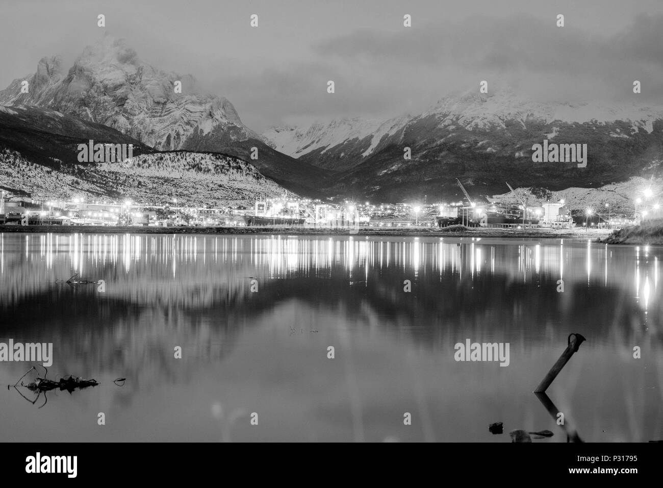 Monte Olivia and nearby mountains look down on the city lights of Ushuaia in the evening. The snow reaches the city and shows winter has started. - Stock Image