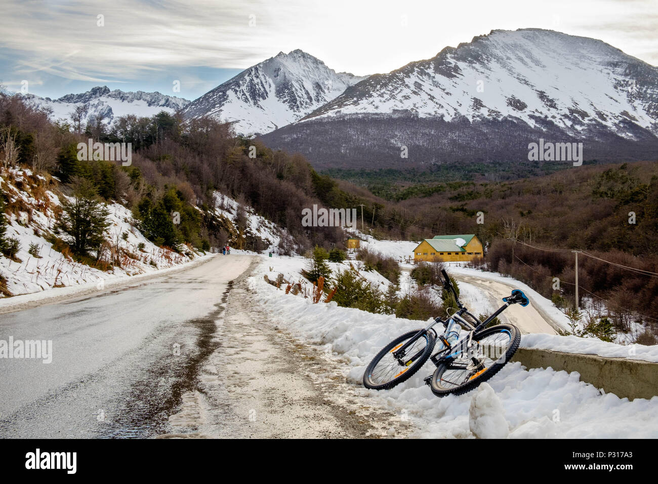 A mountainbike is resting next to the road in between the Martial Glacier and the city of Ushuaia. Snow has made the descent more dangerous. Stock Photo