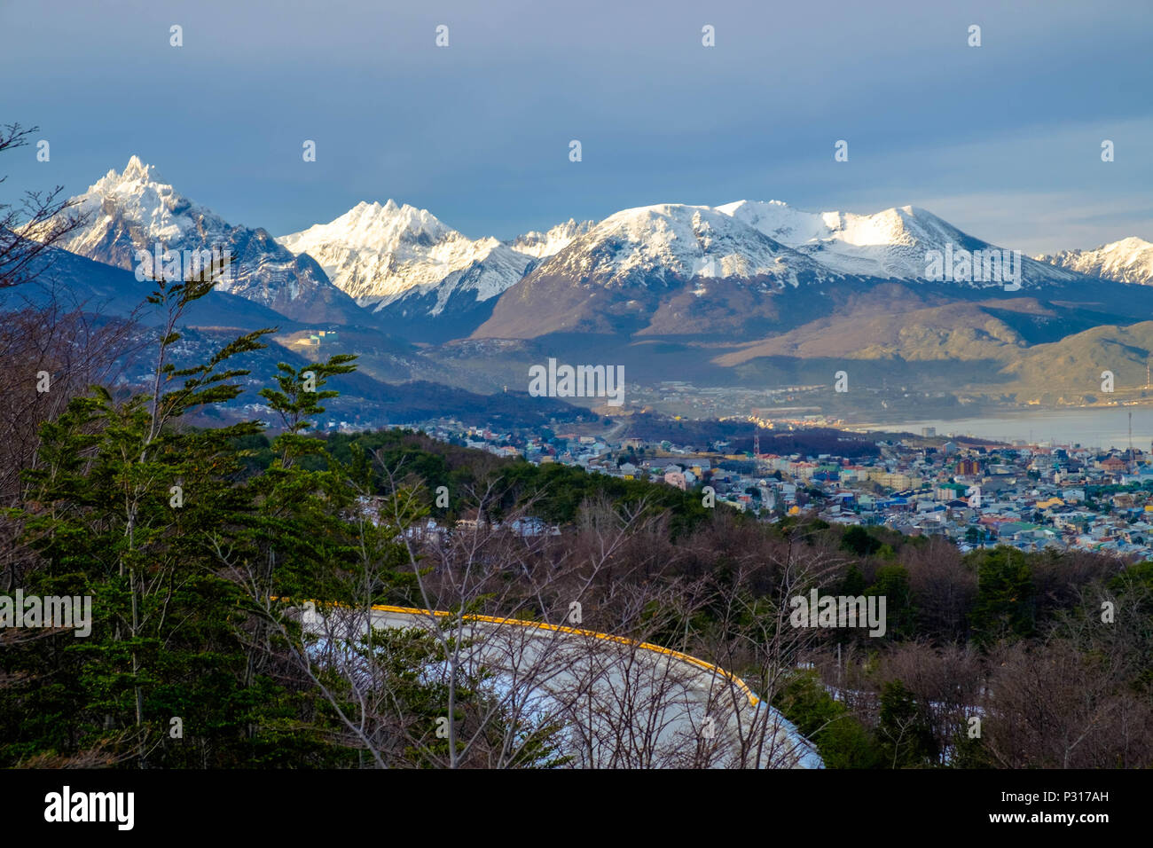 A road full of curves climbs above Ushuaia to the Martial Glacier. Behind the city, you see mountains like Monte Olivia and Monte Cinco Hermanos. Stock Photo