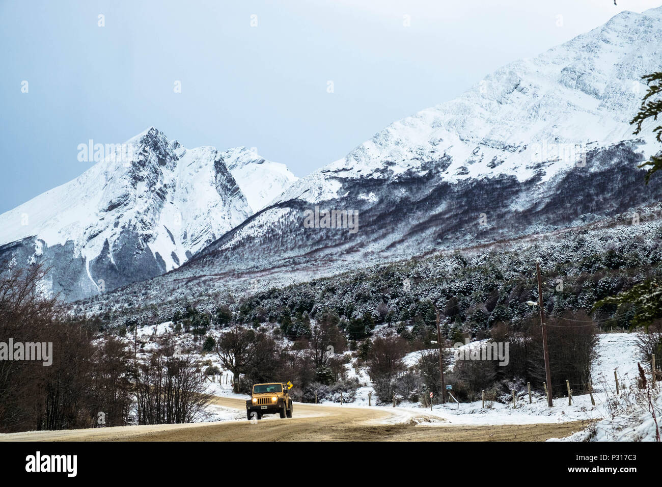 An off-road vehicle drives on the road in between the national park of Tierra del Fuego and Ushuaia. Recent snow gives magic to the landscape. Stock Photo