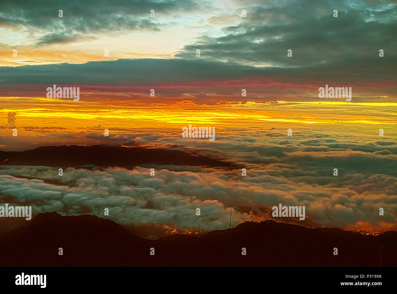 Sunrise as viewed from the top of volcan Baru in Panama. The lights of the city of David are seen below clouds. - Stock Image