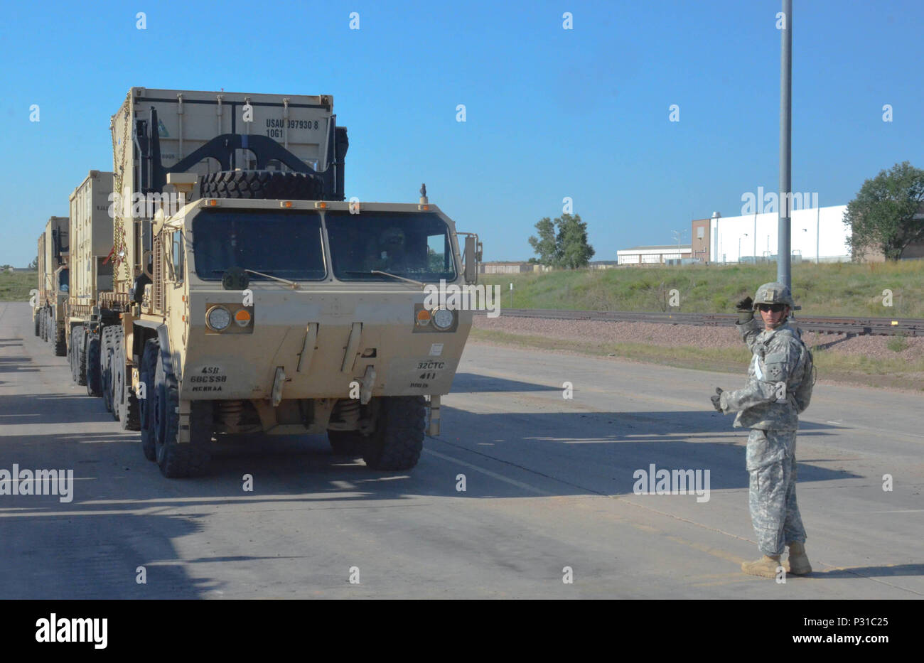 Sgt. Blane Dziolek, 32nd Composite Truck Company, 68th Combat Sustainment Support Battalion, 4th Sustainment Brigade, 4th Infantry Division, ground guides a heavy equipment transport truck at the Fort Carson rail yard Aug. 15. - Stock Image