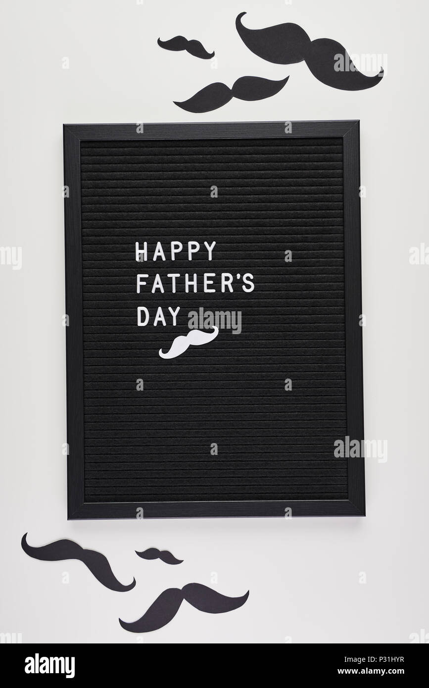 black letterboard with white plastic letters with quote happy fathers day on white background with mustache