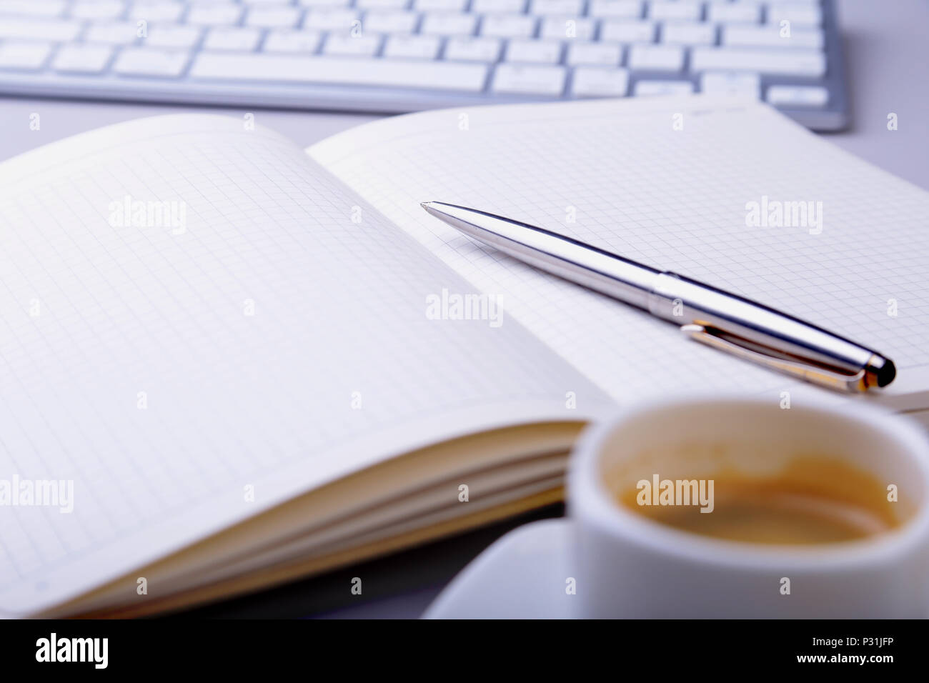 office table with notebook, computer keyboard,, cup of coffee, tablet pc. copy space. Stock Photo