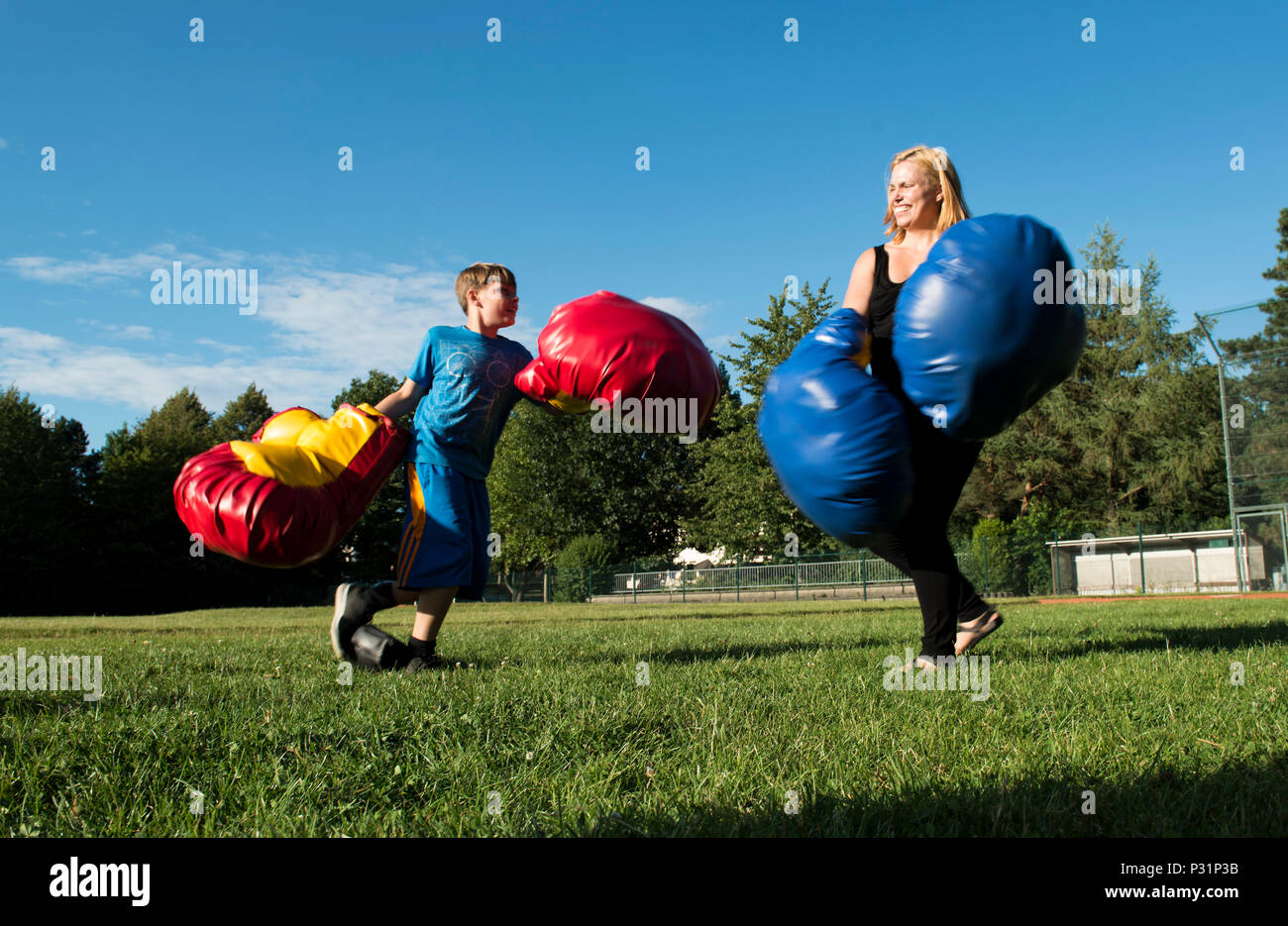 """A Kaiserslautern Military Community member and her son box during the Ramstein and Vogelweh Community Center's Olympic Family Night Aug. 22, 2016 at Ramstein Air Base, Germany. To earn a medal, children also participated in sumo wrestling, basketball, a three-legged race, a potato sack race and a """"ski race"""". (U.S. Air Force photo/Senior Airman Tryphena Mayhugh) - Stock Image"""