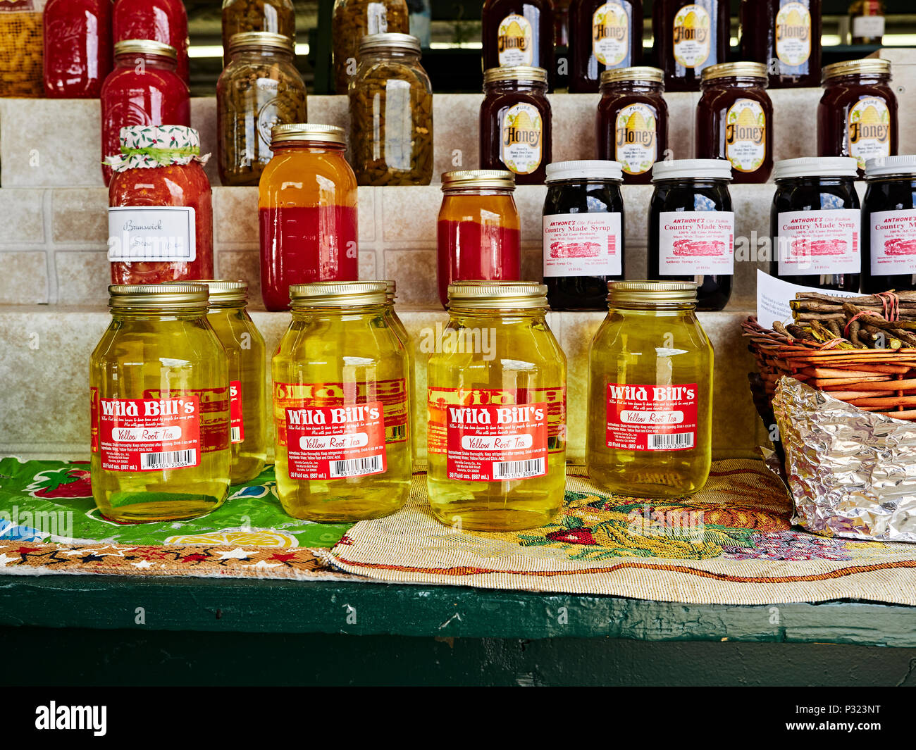 Jars of Yellow Root Tea, a homemade alternative medicine for some, or a home remedy or homeopathic treatment on display at an indoor farmer's market. - Stock Image