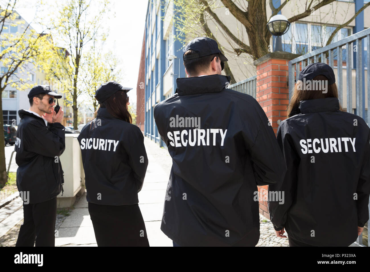 Rear View Of Security Guards In Black Uniform Standing Outside Building - Stock Image