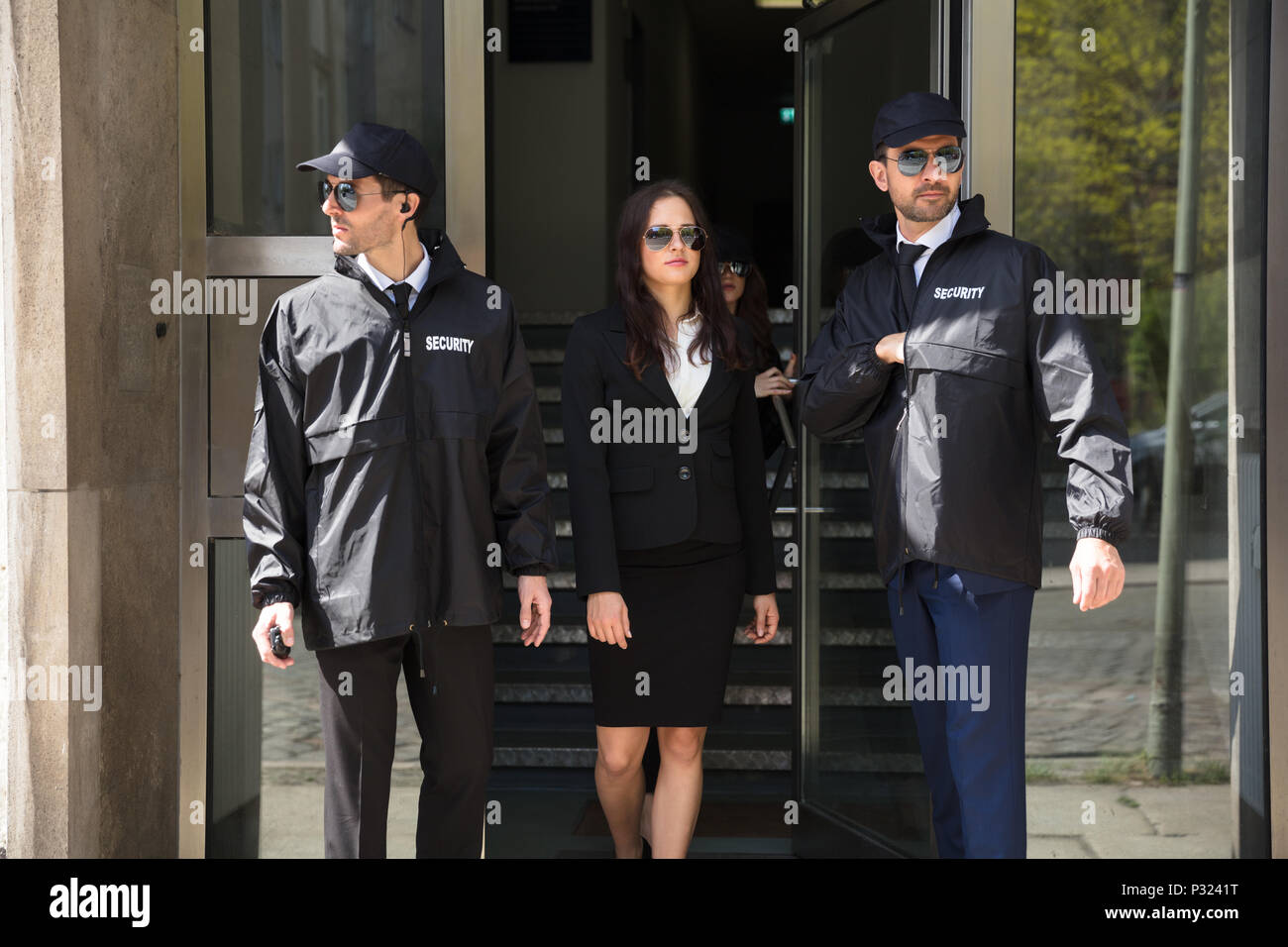 Young Businesswoman Stepping Out From Office Building With Her Bodyguards - Stock Image