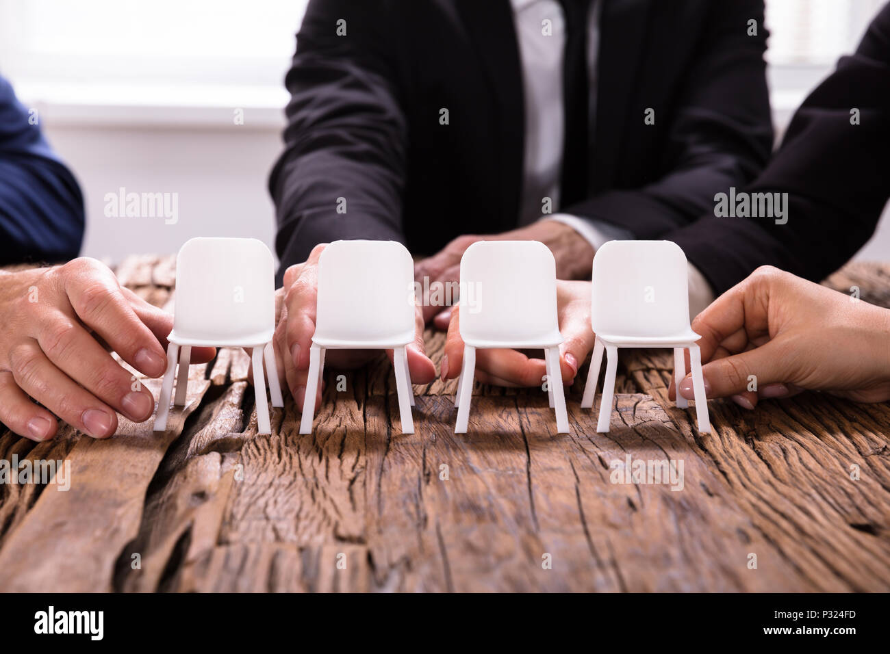 Close-up Of A Businesspersons's Hands Arranging Chairs In A Row Stock Photo